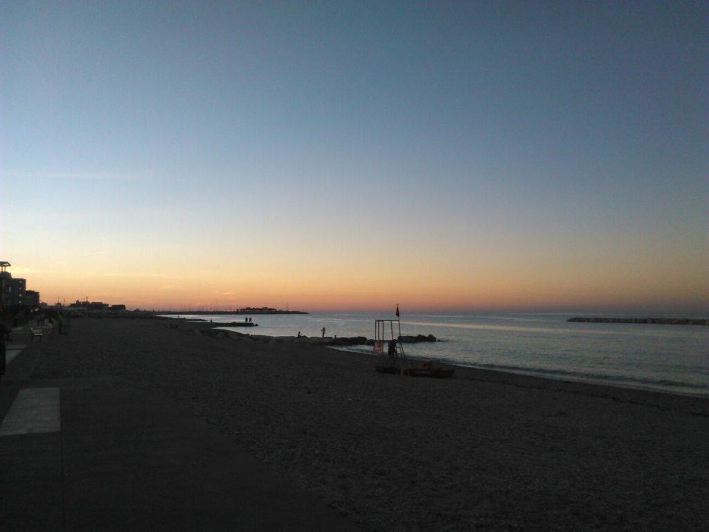 La spiaggia Sassonia al tramonto con la Marina dei Cesari sullo sfondo
